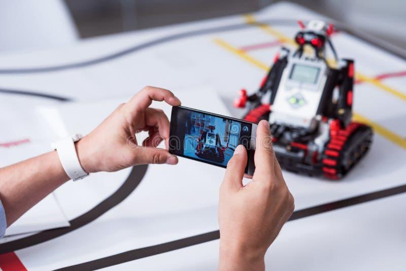Photoshooting de peu de robot mignon situé sur la table photos stock