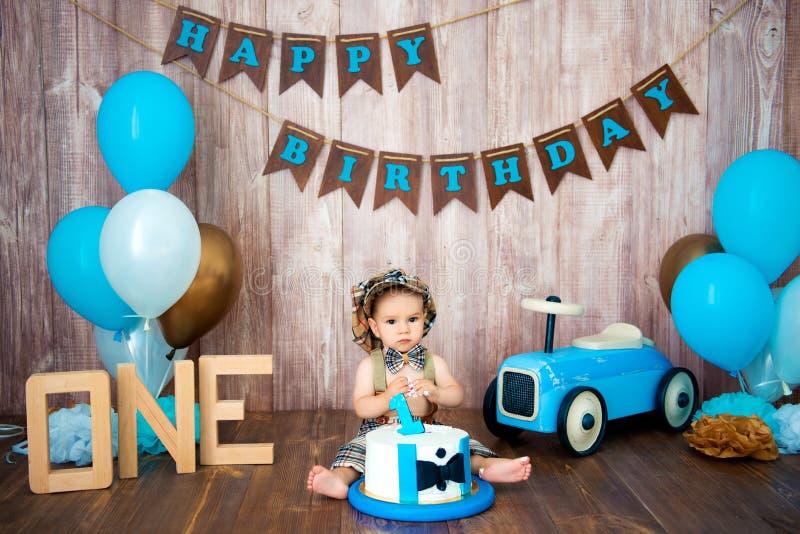 Photoshootverbrijzeling smashcake voor een kleine jongensheer Verfraaide photozone met een houten retro auto en heliumballons gel stock fotografie