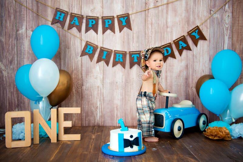 Photoshootverbrijzeling smashcake voor een kleine jongensheer Verfraaide photozone met een houten retro auto en heliumballons gel royalty-vrije stock afbeelding
