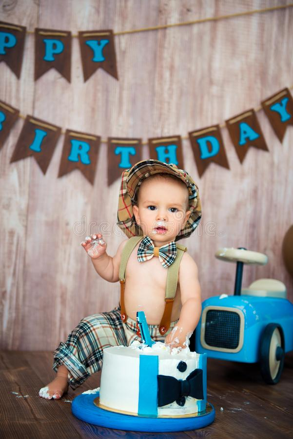 Photoshootverbrijzeling smashcake voor een kleine jongensheer Verfraaide photozone met een houten retro auto en heliumballons gel stock afbeeldingen