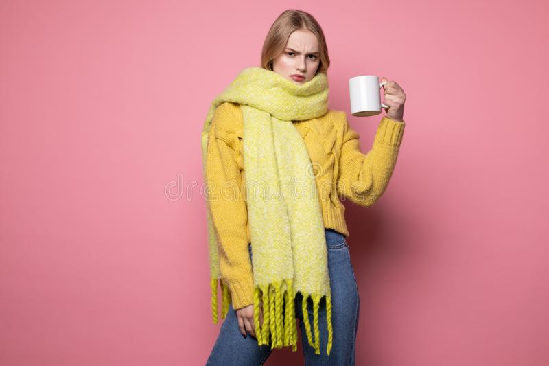 Photot of unhappy blonde girl in yellow sweater and scarf, with cup of coffe stock photography
