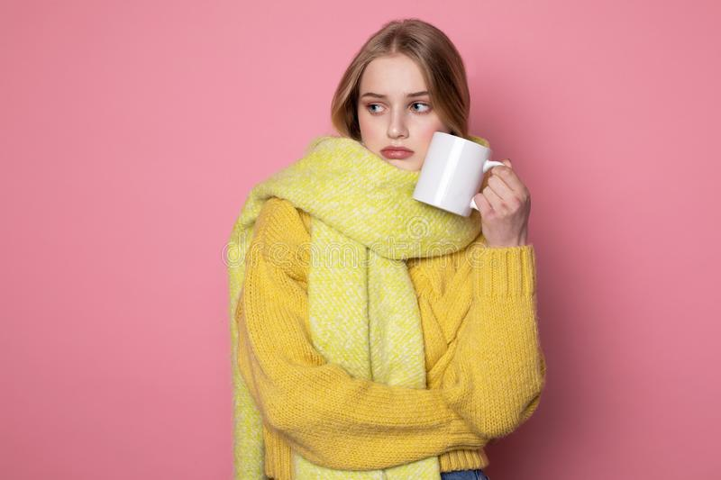 Photot of unhappy blonde girl in yellow sweater and scarf, with cup of coffe royalty free stock image