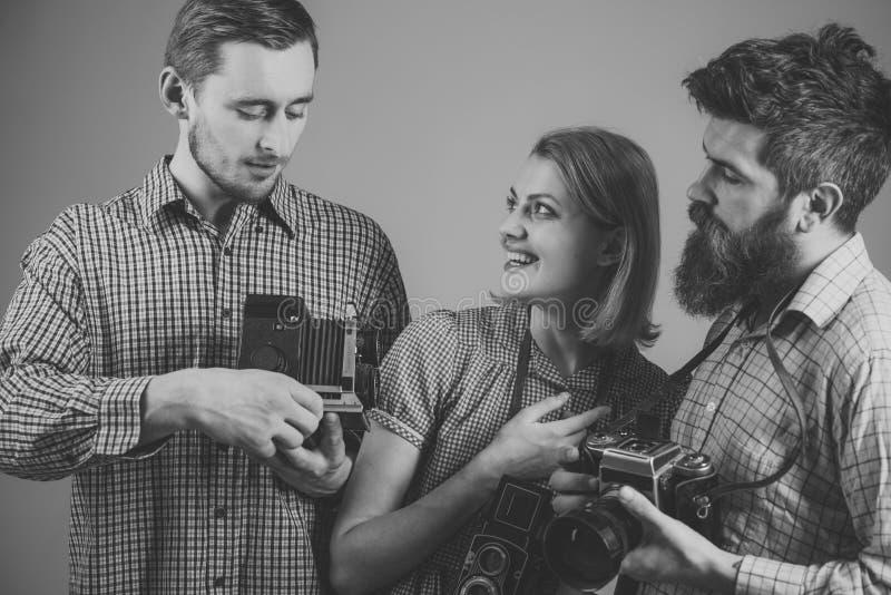 Phototraining Οι άνδρες, γυναίκα στα πρόσωπα χαμόγελου εξετάζουν τη κάμερα, γκρίζο υπόβαθρο Άτομα στα ελεγμένα ενδύματα, αναδρομι στοκ εικόνες