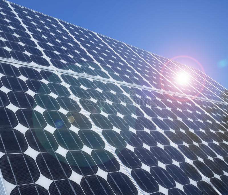 Photovoltaic cells solar panels lens flare. Solar panel photovoltaic cells array close up with blue sky lens flare and copy space. Solar energy is an ecofriendly stock photography