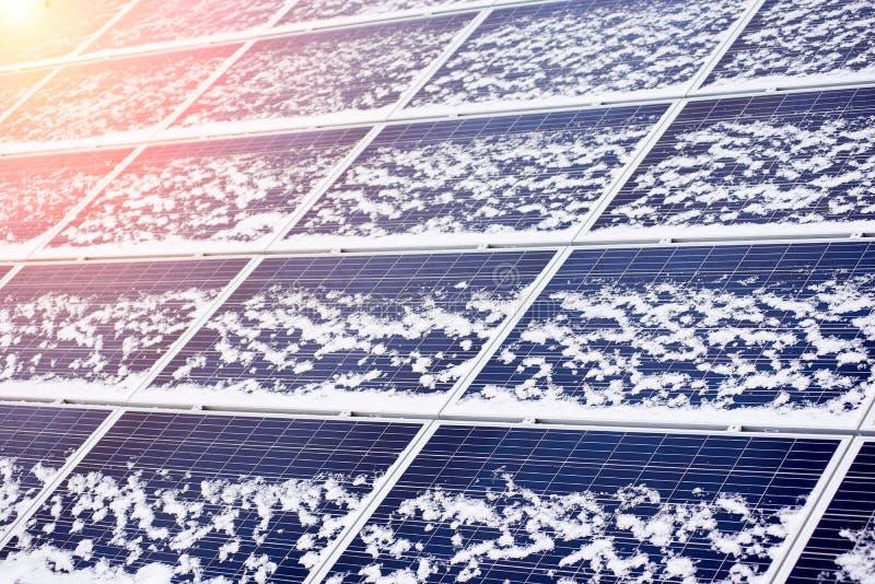 Photovoltaic ecologische die modules lichtjes door sneeuw worden geblazen royalty-vrije stock afbeeldingen
