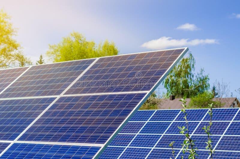 Photovoltaic ecologische modules op groene grasvallei tegen van zon en bewolkte hemel stock foto