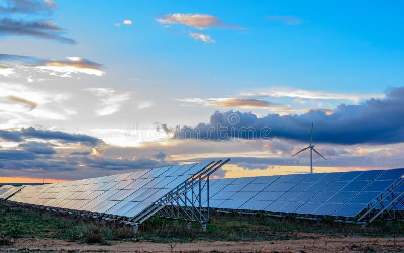 Photovoltaic och vindväxt på solnedgången royaltyfria bilder