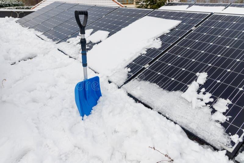 Photovoltaic panelen op het dak met sneeuw, met een sneeuwschop in de winter stock afbeelding
