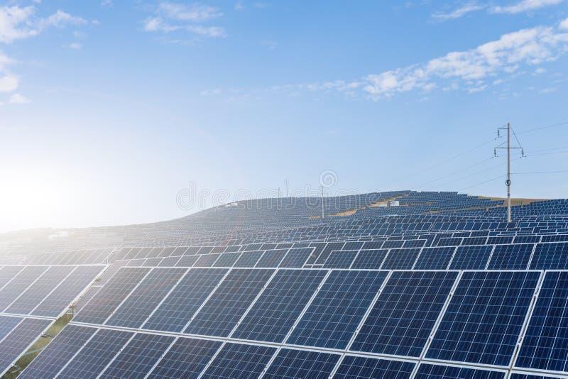 Photovoltaic paneler och över huvudet överföringslinjer arkivfoton