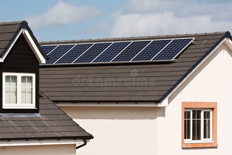 Photovoltaic solpaneler på det belade med tegel taket arkivbild