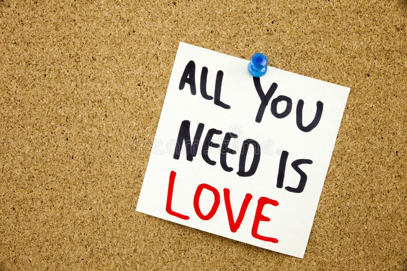 A yellow sticky note writing, caption, inscription Phrase ALL YOU NEED IS LOVE in black ext on a sticky note pinned to a cork noti royalty free stock image