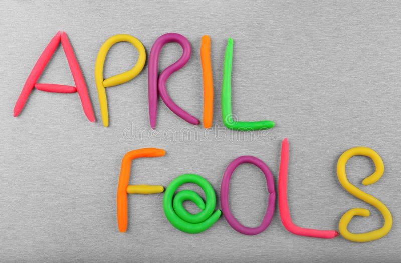 Phrase `April fools` made from plasticine. On grey background royalty free stock image