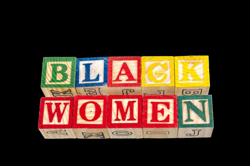 The phrase black women displayed on a black background. The term black women visually displayed on a black background using colorful wooden toy blocks image with stock images