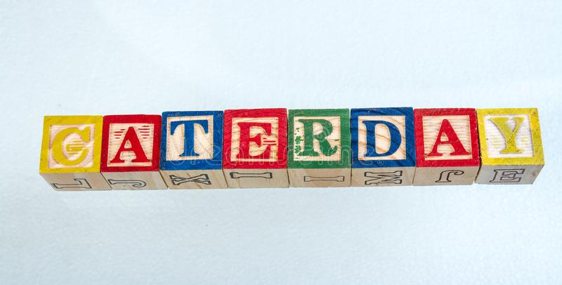 The phrase caterday displayed on a white background. The term caterday visually displayed on a white background using colorful wooden toy blocks image with copy stock photography