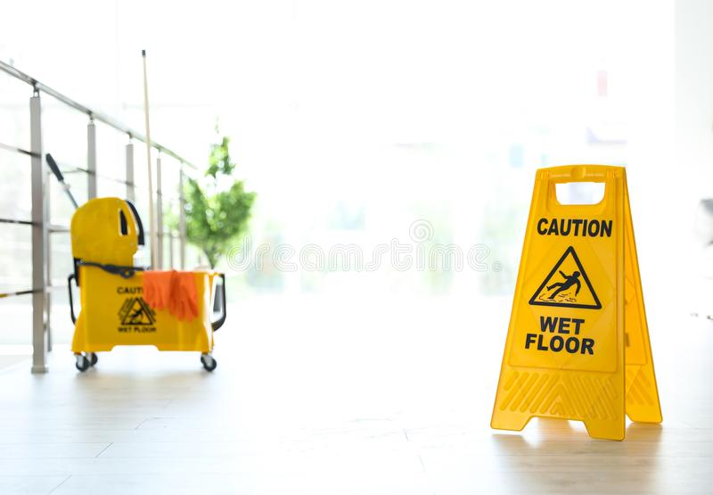 Phrase CAUTION WET FLOOR on safety sign and yellow mop bucket with cleaning supplies, indoors. Phrase CAUTION WET FLOOR on safety sign and mop bucket with royalty free stock photos