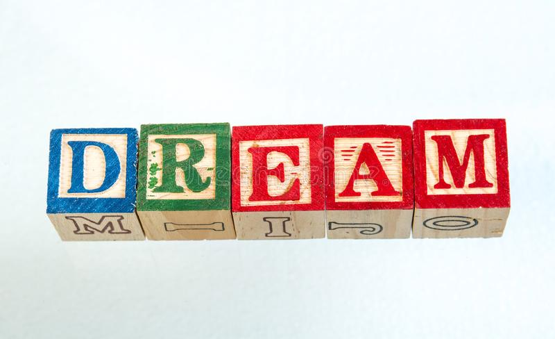 The phrase dream displayed on a white background. The term dream visually displayed on a white background using colorful wooden toy blocks image with copy space stock photos