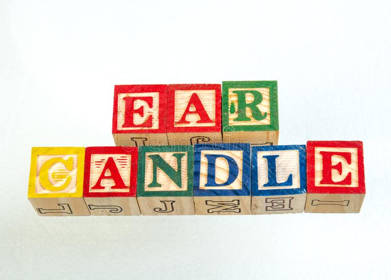 The phrase ear candle displayed on a white background. The term ear candle visually displayed on a white background using colorful wooden toy blocks image with royalty free stock images