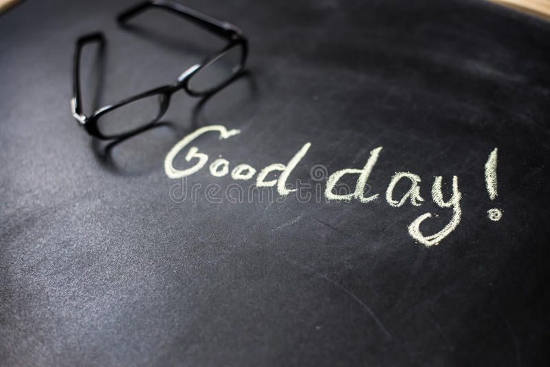 The phrase Good day on the blackboard. With chalk stock photography
