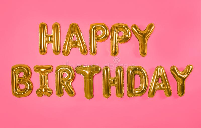 Phrase HAPPY BIRTHDAY made of foil balloon letters. On pink background stock photos