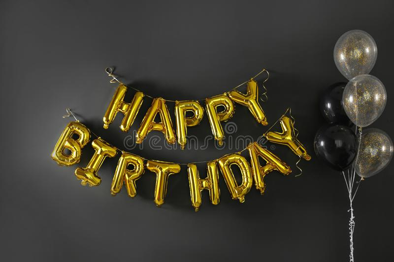 Phrase HAPPY BIRTHDAY made of golden balloon letters on black stock image