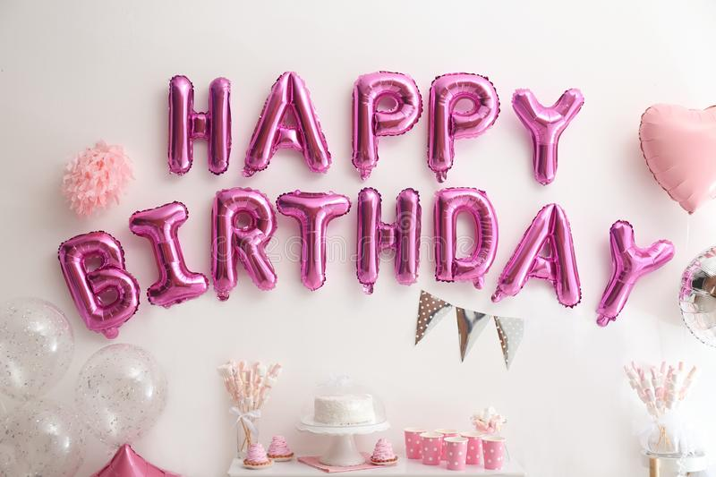 Phrase HAPPY BIRTHDAY made of balloon letters on white wall. Phrase HAPPY BIRTHDAY made of pink balloon letters on white wall royalty free stock image
