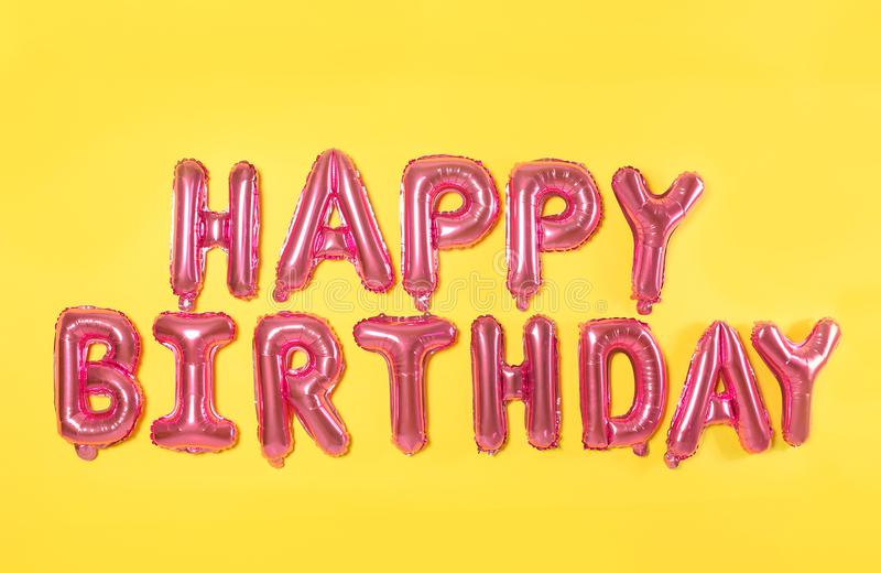 Phrase HAPPY BIRTHDAY made of pink foil balloon letters on background. Phrase HAPPY BIRTHDAY made of pink foil balloon letters on yellow background stock image