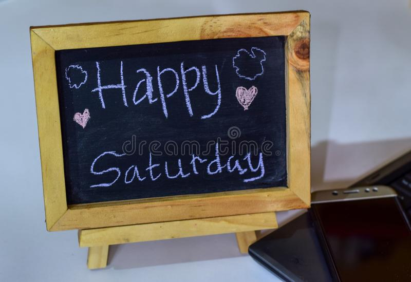 Phrase Happy saturday written on a chalkboard on it and smartphone, laptop stock image