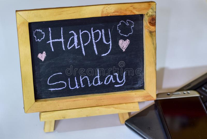 Phrase Happy sunday written on a chalkboard on it and smartphone, laptop royalty free stock photos