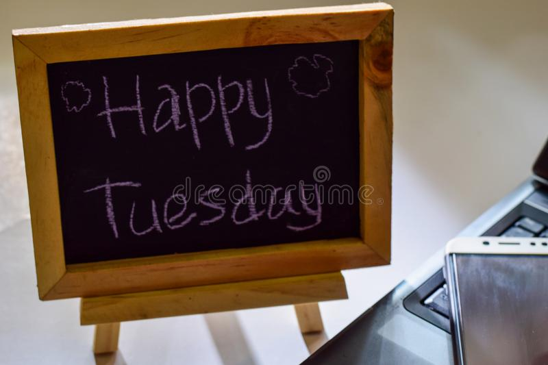 Phrase happy tuesday written on a chalkboard on it and smartphone, laptop royalty free stock photography
