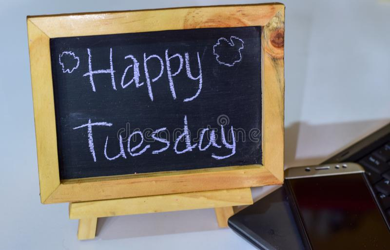 Phrase happy tuesday written on a chalkboard on it and smartphone, laptop stock image
