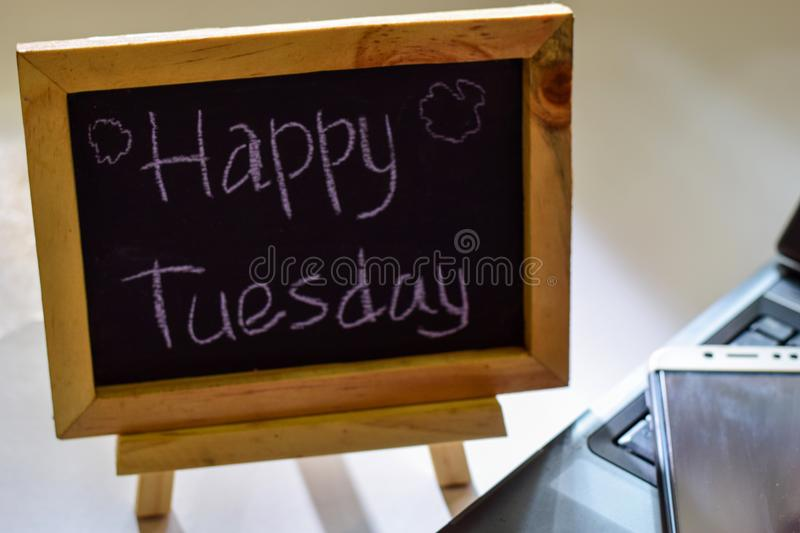 Phrase happy tuesday written on a chalkboard on it and smartphone, laptop stock photo