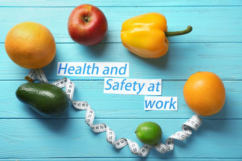 Phrase \'Health and safety at work\', fruits and measuring tape on wooden background royalty free stock photo