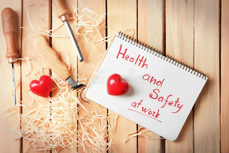 Phrase Health and safety at work written in notebook, tools and red hearts on wooden background stock image