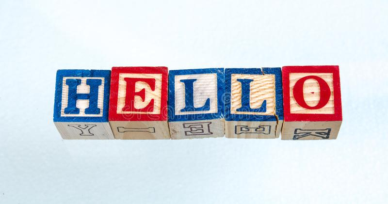 The phrase hello displayed on a white background. The term hello visually displayed on a black background using colorful wooden toy blocks image with copy space stock photos
