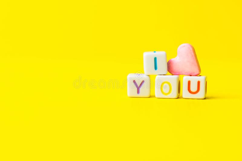 Phrase I Love You constructed from white letter cubes and pink heart shape sugar candy on bright yellow background. Valentine royalty free stock photo
