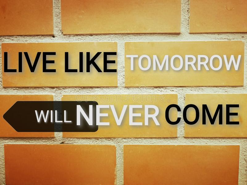 Phrase live like​ tomorrow​ will​ never​ come​ on brick wall royalty free stock photography