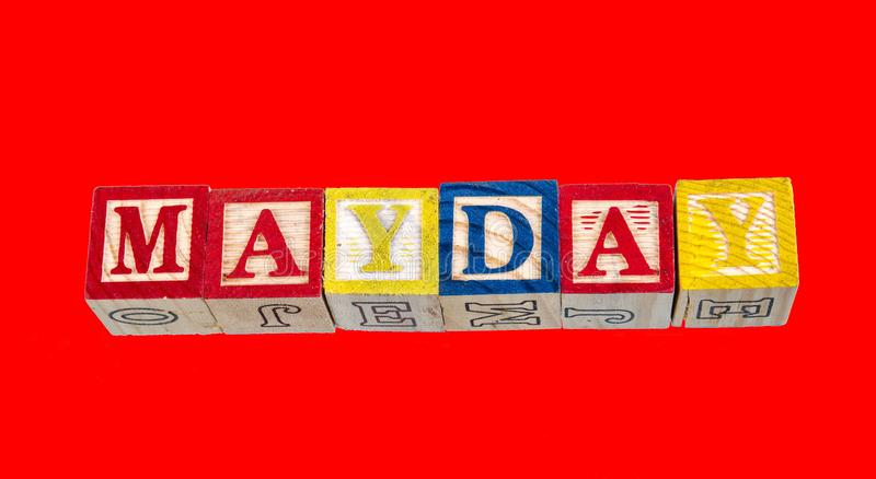 The phrase Mayday displayed on a red background. The phrase Mayday visually displayed using colorful wooden toy blocks on a red background image with copy space stock photo