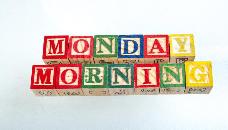 The phrase Monday morning displayed on a white background. The term Monday morning visually displayed on a white background using colorful wooden toy blocks stock photo