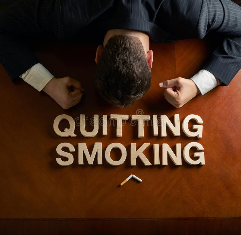 Phrase Quitting Smoking and devastated man. Phrase Quitting Smoking made of wooden block letters and devastated middle aged caucasian man in a black suit sitting stock photography