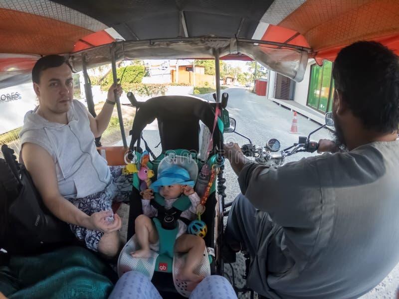PHUKET, ΤΑΪΛΆΝΔΗ - 19 ΦΕΒΡΟΥΑΡΊΟΥ 2019: Η επισφαλής μεταφορά ενός μικρού παιδιού σε έναν περιπατητή μωρών σε μια δίτροχο χειράμαξ στοκ φωτογραφίες