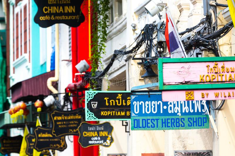 Business signboards along a street in the old town of Phuket in Thailand. Phuket, Districtul Mueang Phuket / Thailand - August 3, 2019: Business signboards along stock photos