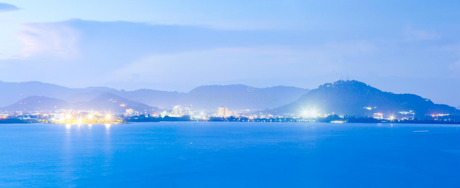 Phuket Island at twilight. Beautiful modern city with light, mountains and sunset sky backgrounds, twilight reflecting in the sea royalty free stock image
