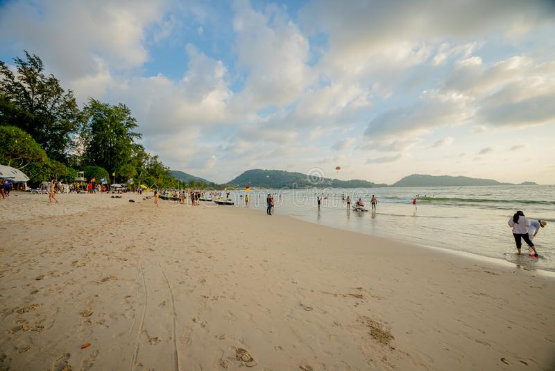 Phuket Juli 09, 2019: Det oidentifierade folket kopplar av på den Patong stranden under en solig dag i Phuket, Thailand Patong är arkivfoto
