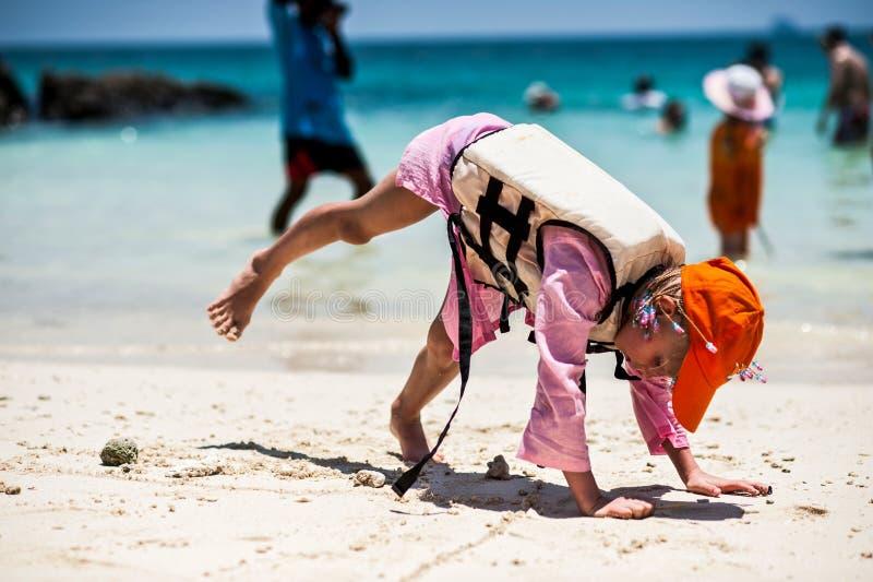 PHUKET - MARS 16: Lycklig flicka för litet barn som spelar i stranden MARS royaltyfri foto