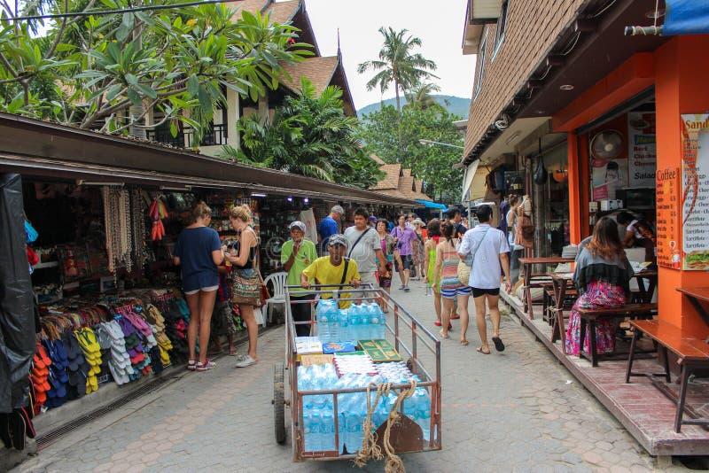 PHUKET, TAILÂNDIA 29 DE NOVEMBRO DE 2013: Os turistas compram na rua de passeio do mercado velho da cidade Koh PhiPhi Don no mar  imagem de stock royalty free