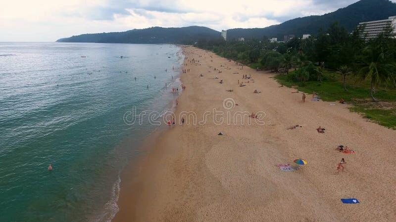 PHUKET, TAILÂNDIA - 20 DE JANEIRO DE 2017: Voo sobre a praia vazia e as poucas pessoas que andam e que têm o sunbath na praia imagens de stock royalty free
