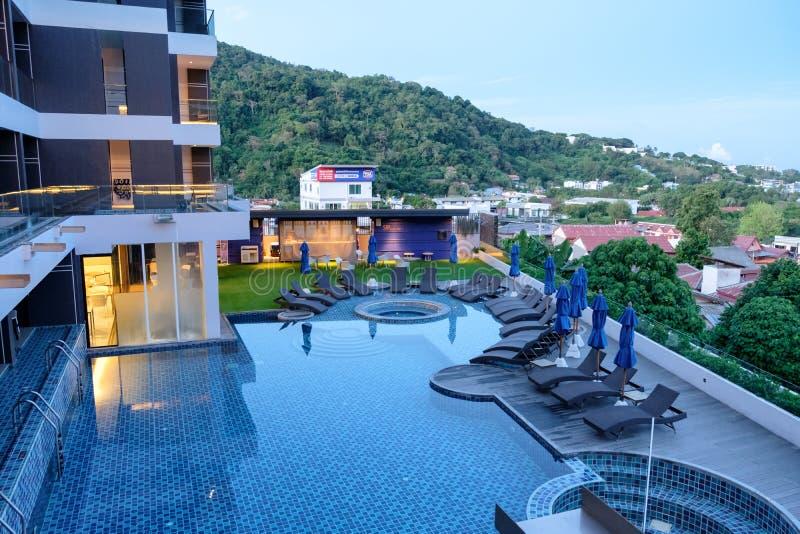 Phuket, Tailandia - 4 de abril de 2017: Balcón del hotel y piscina con los sunbeds en el hotel del yama foto de archivo libre de regalías