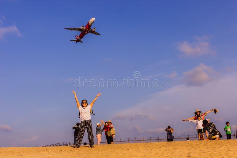 Phuket, Tailandia - 14 de abril de 2019: Los turistas gozan el tomar de una imagen con el aeroplano que vuela sobre ellos como el fotografía de archivo libre de regalías