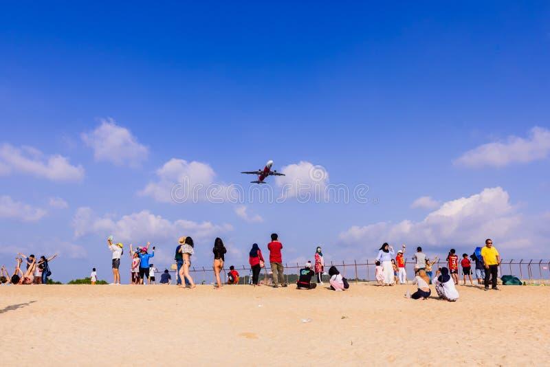 Phuket, Tailandia - 14 de abril de 2019: Los turistas gozan el tomar de una imagen con el aeroplano que vuela sobre ellos como el fotos de archivo