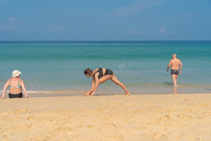 Phuket, Tailandia - 30 de marzo de 2019: Muchacha delgada en un bañador negro con un tatuaje en su hombro que hace la yoga Pilate imagenes de archivo